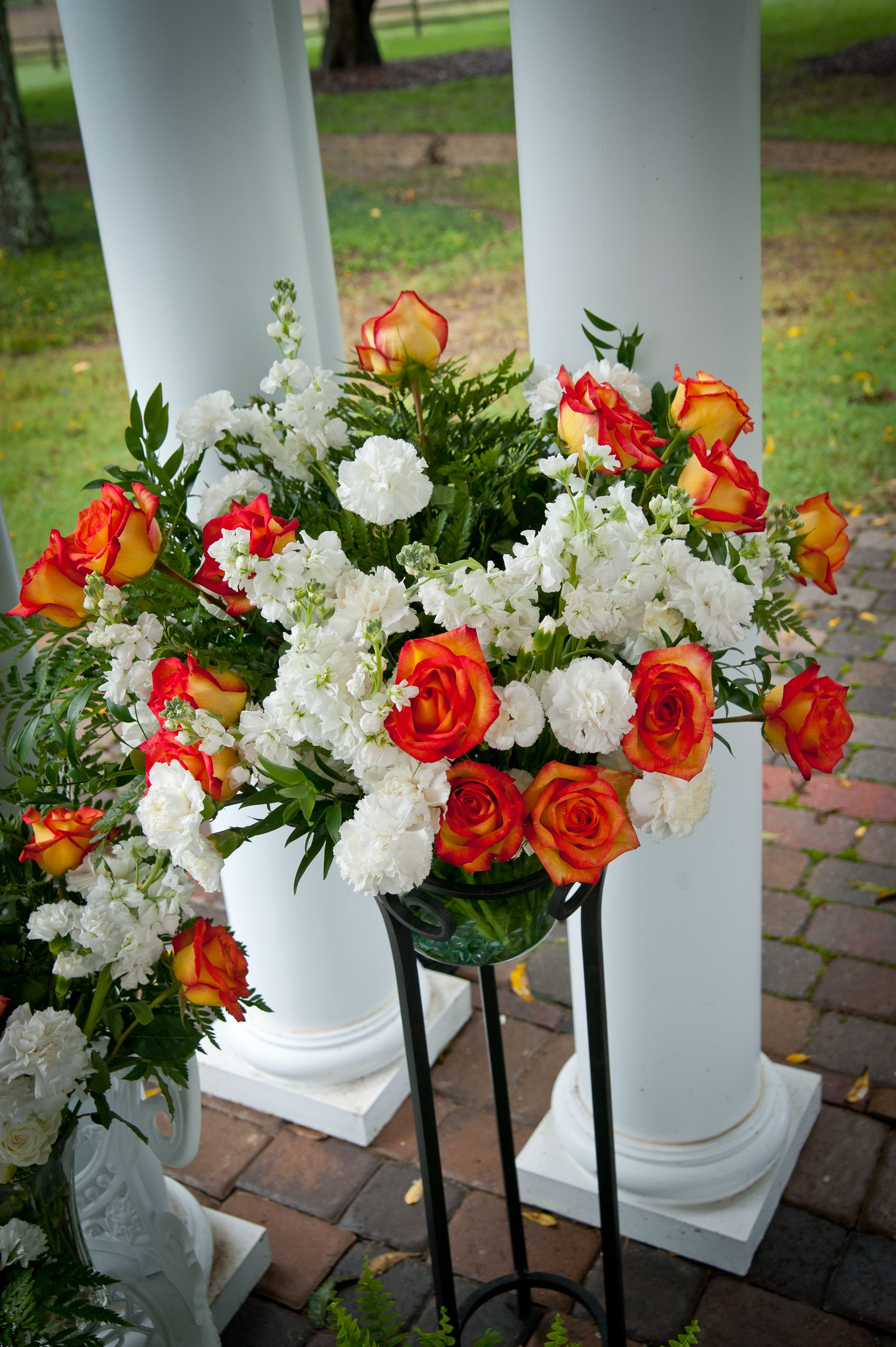 Orange roses with mixed white flowers in wedding ceremony decor. Erin and Dan's wedding at Lenora's Legacy. Image credit: Famzing.