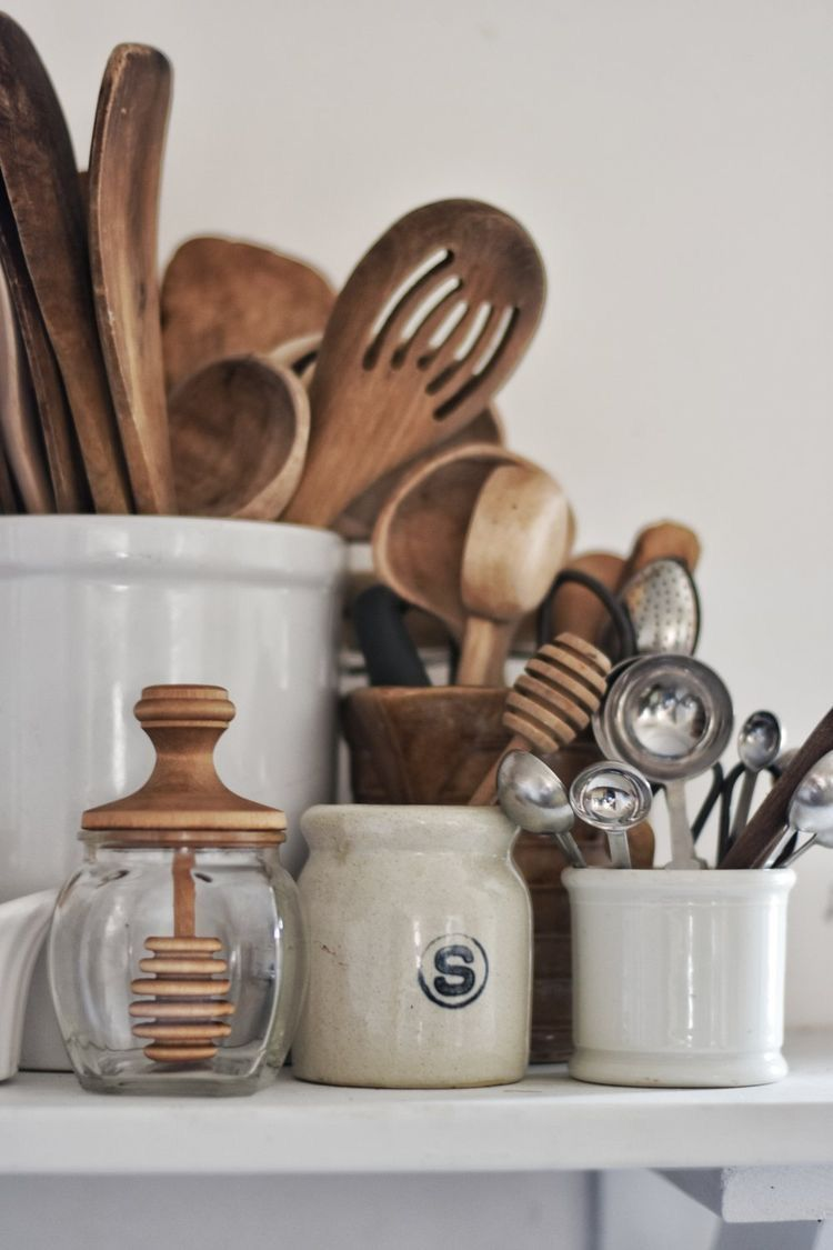 wooden kitchen spoons, spatulas, other tools organized in stoneware and glass containers