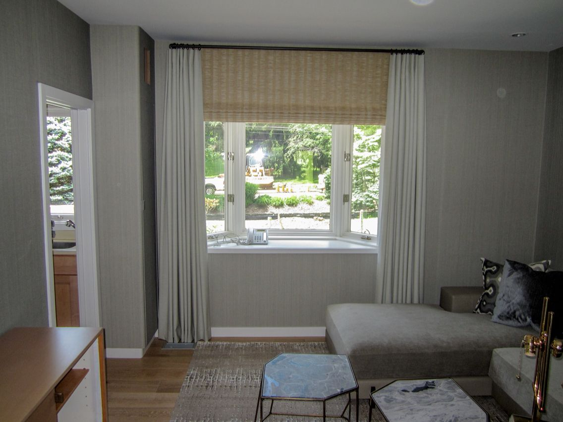 Cream heavy drapery and a textured roman shade cover up this living ...