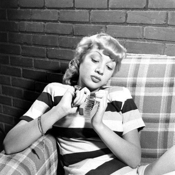 Actress Olga San Juan demonstrating nail brush.