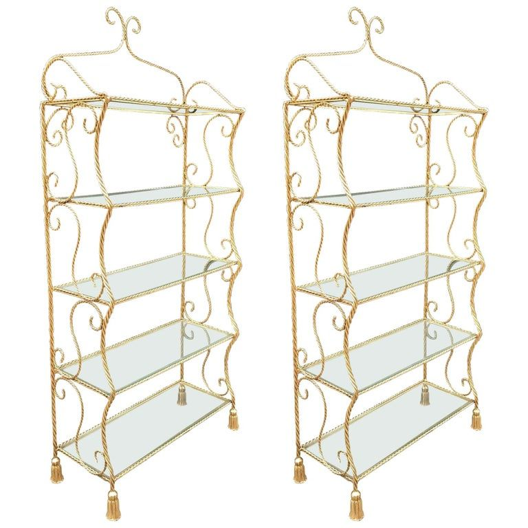 Pair of Italian gilt metal rope and tassel etageres with five glass shelves.