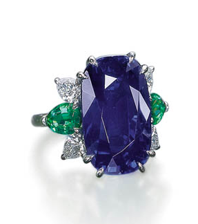 A SAPPHIRE RING   Set with a cushion-shaped sapphire weighing 22.28 carats to the pear-shaped emerald and diamond three-stone shoulders and 18k white gold hoop