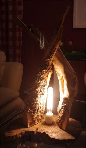 Lampada da tavolo in legno ealizzata su una fetta di tronco dalla quale si di...