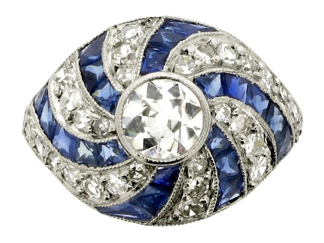 Sapphire and diamond spinning wheel ring, circa 1930. A platinum ring set with one central round old cut diamond in a millegrain collet setting with an approximate weight of 0.75 carats, surrounded by a bombé bezel with integrated shoulders composed of a swirling design of six curved rays of twenty two tapered French cut sapphires in millegrain channel settings with an approximate total weight of 1.50 carats, alternated with six curved rays of thirty round eight cut diamonds in millegrain…