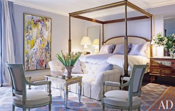 """Thomas Britt told Architectural Digest that he """"pumped the blue up"""" in this master bedroom. """"The whole trick with these paint treatments is that you have to try them out in the actual space,"""" he says, """"then check how the light reflects off the walls and the ceiling."""" The cream, blue and orange dhurrie rug adds a watery pattern that amplifies the blues of the walls and drapes and also stands up to the bright yellow and reds in the abstract painting."""
