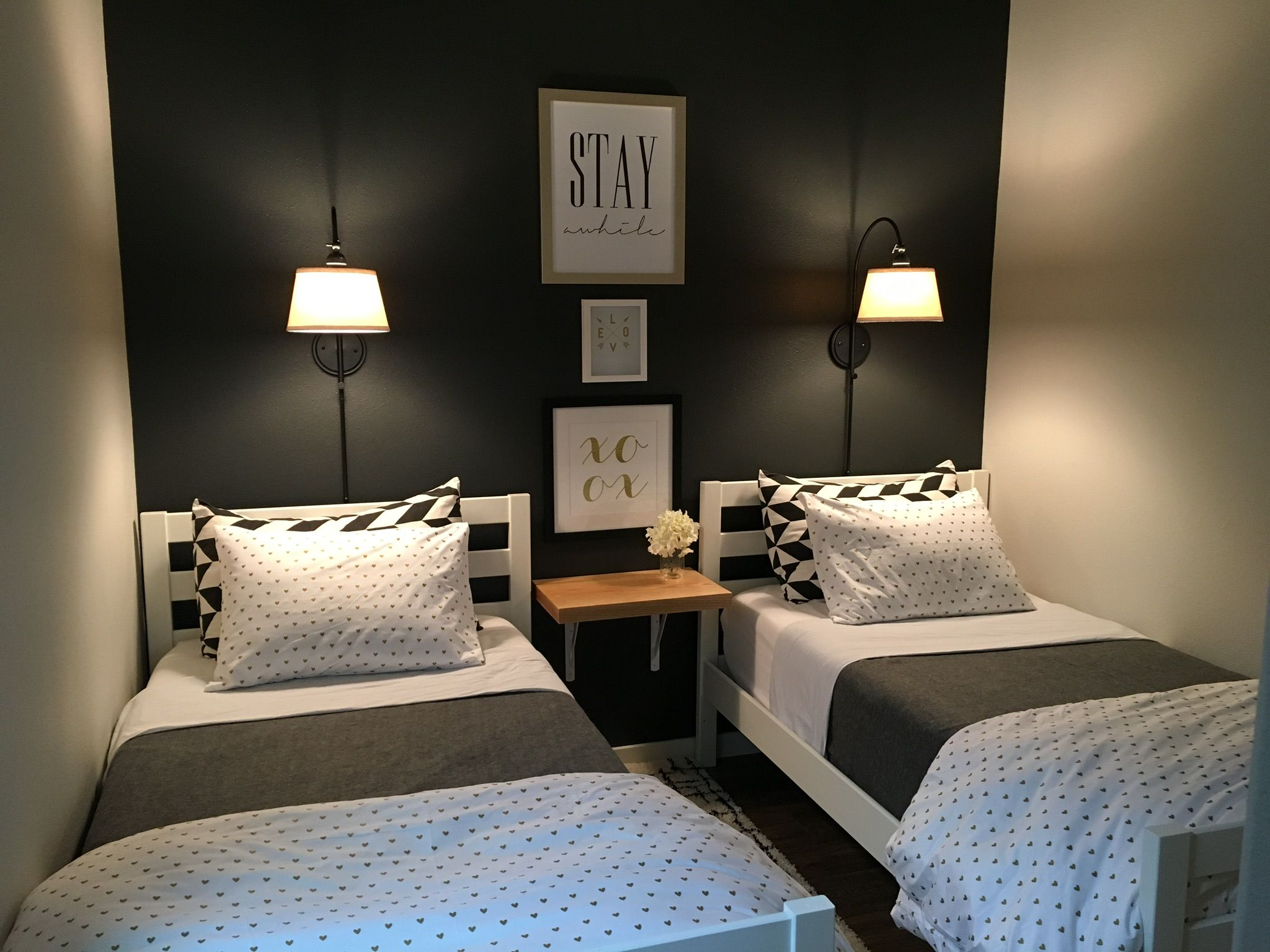 small guest room with two twin beds wall lig