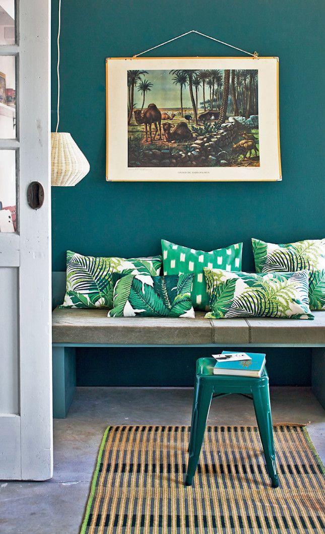 Green wall + palm pillows.