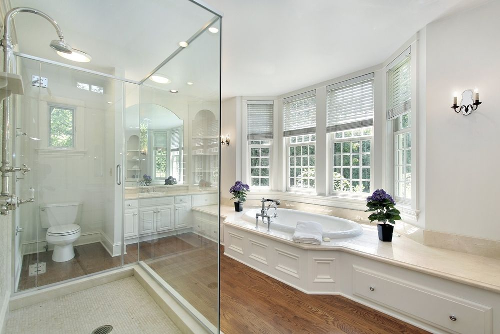We love how the soaking tub sits in front of a large bay window on a raised platform that extends across the bathroom! It is great for storage space! Find the 34 Luxury White Master Bathroom Ideas gallery at http://www.homestratosphere.com/luxury-white-bathroom-designs/#utm_sguid=163048,256b8623-3f55-996d-cc42-fa91887fa581 See 100s more bathroom designs at http://www.homestratosphere.com/category/bathrooms/#utm_sguid=163048,256b8623-3f55-996d-cc42-fa91887fa581