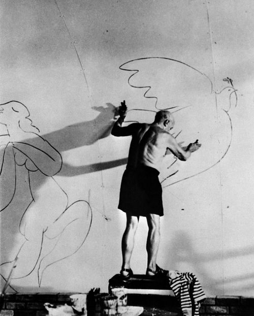 Pablo Picasso drawing a dove of peace on a wall in his