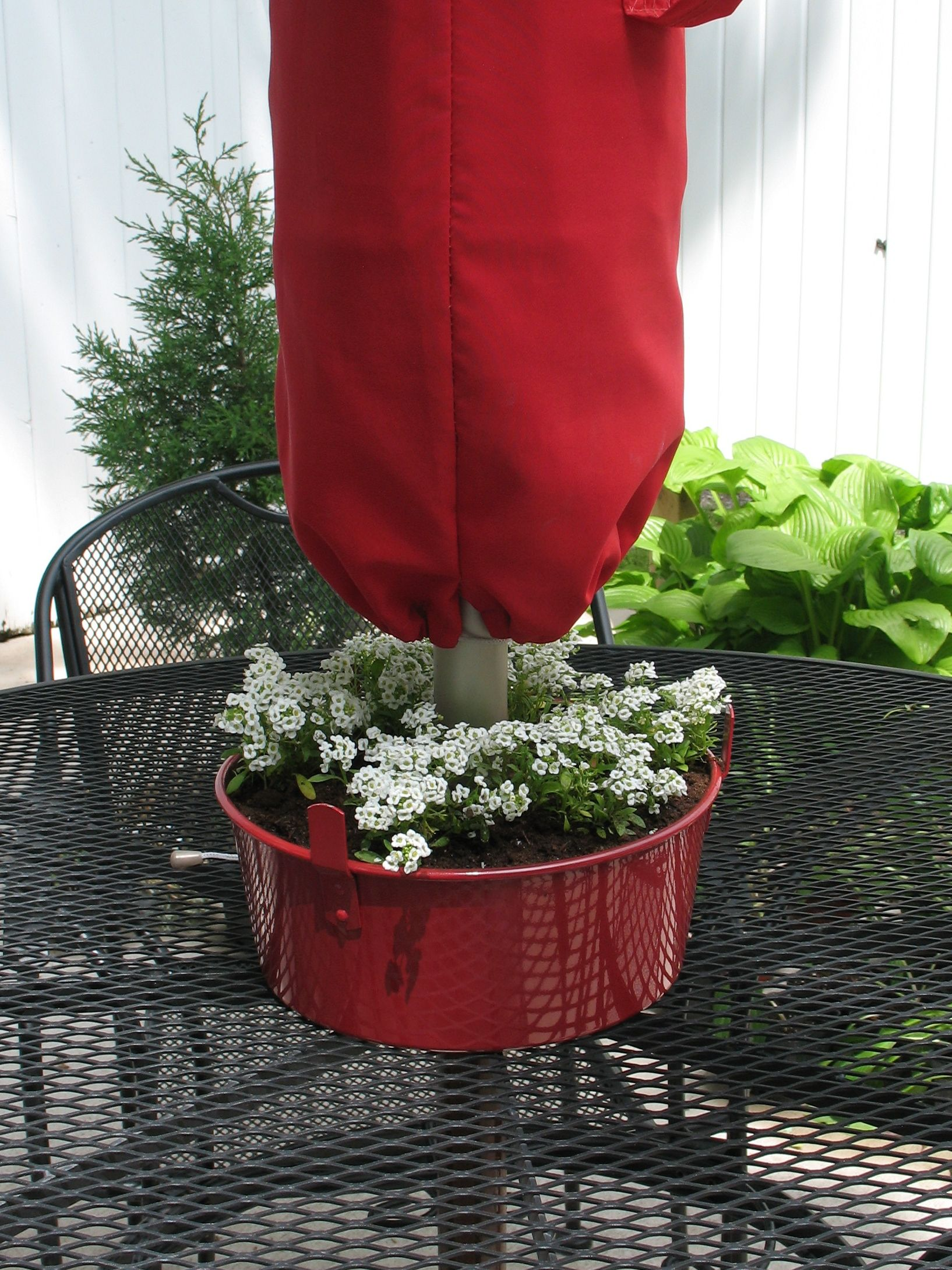 Patio tabletop planter made from an angel food cake pan. Umbrella pole fits through the hole in the center of the pan. Pan from a local thrift shop for a buck. Paint, plant, enjoy!