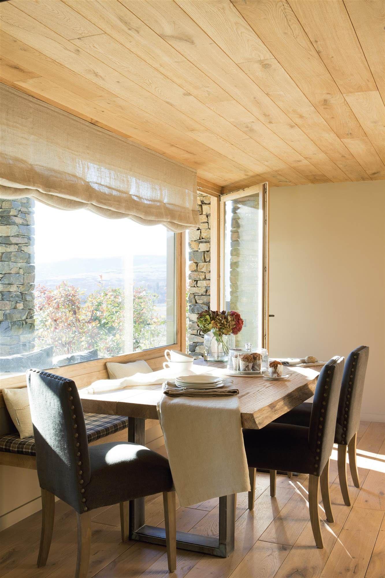 Comedor revestido de madera con una mesa, sillas y un banco en un ...