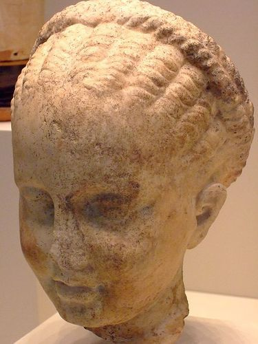 Head of a girl whose braided hairstyle identify her as an assistant in the worship of Artemis Greek about 300 BCE Marble