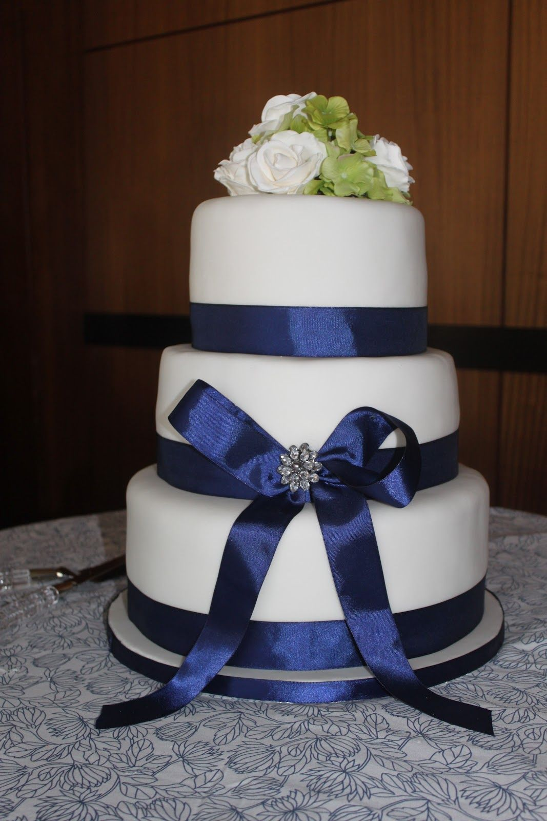 wedding cake with Navy blue ribbon and lime green flowers