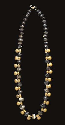 A SYRIAN BANDED AGATE AND GOLD BEAD NECKLACE   CIRCA 5TH CENTURY B.C.   Compose of forty-three globular banded agate beads, the central portion interspersed with twenty gold pendant beads; strung with a modern S-hook closure  24 13/16 in. (63 cm.) long