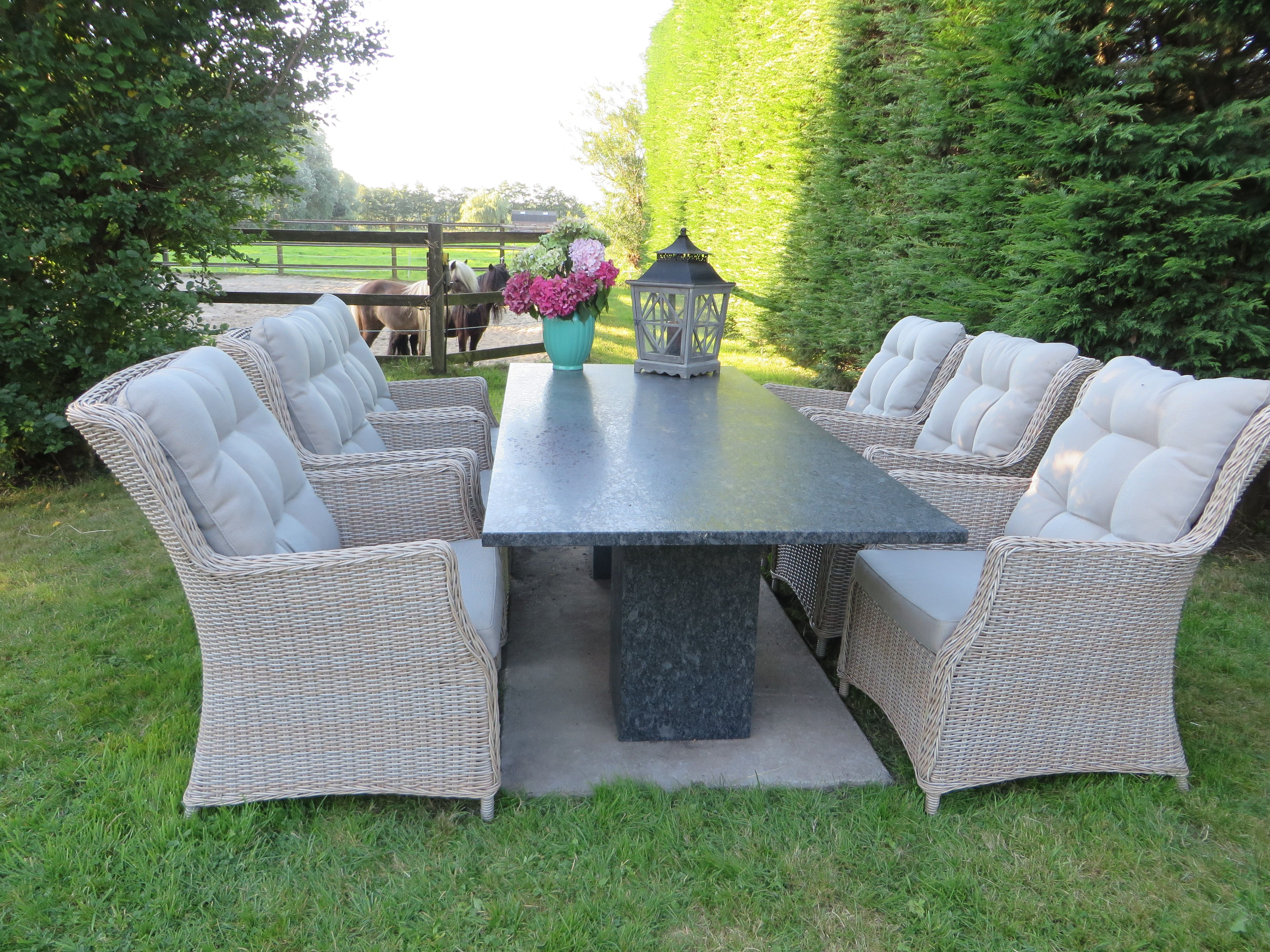 Tuinset met tafel van graniet met zes ruime gevlochten stoelen