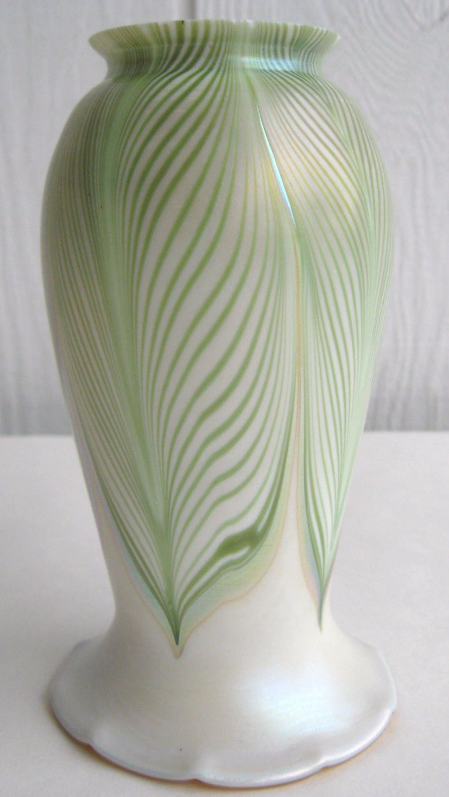 vintage FOSTORIA art glass lamp or light shade with an iridescent pullled feather pattern or design. The shade has a rich pearl or pearlized background with a green pulled feather the ends in an iridescent gold aurene or soft light marigold color that matches the interior of the shade.