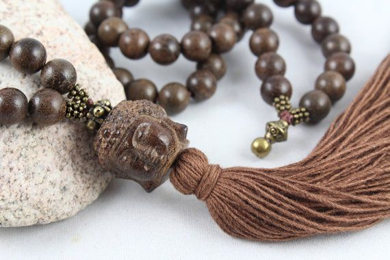 A serene carved wood Buddha is the focal or guru bead on this strand of natural dark wood beads made from agarwood. They have a very slight