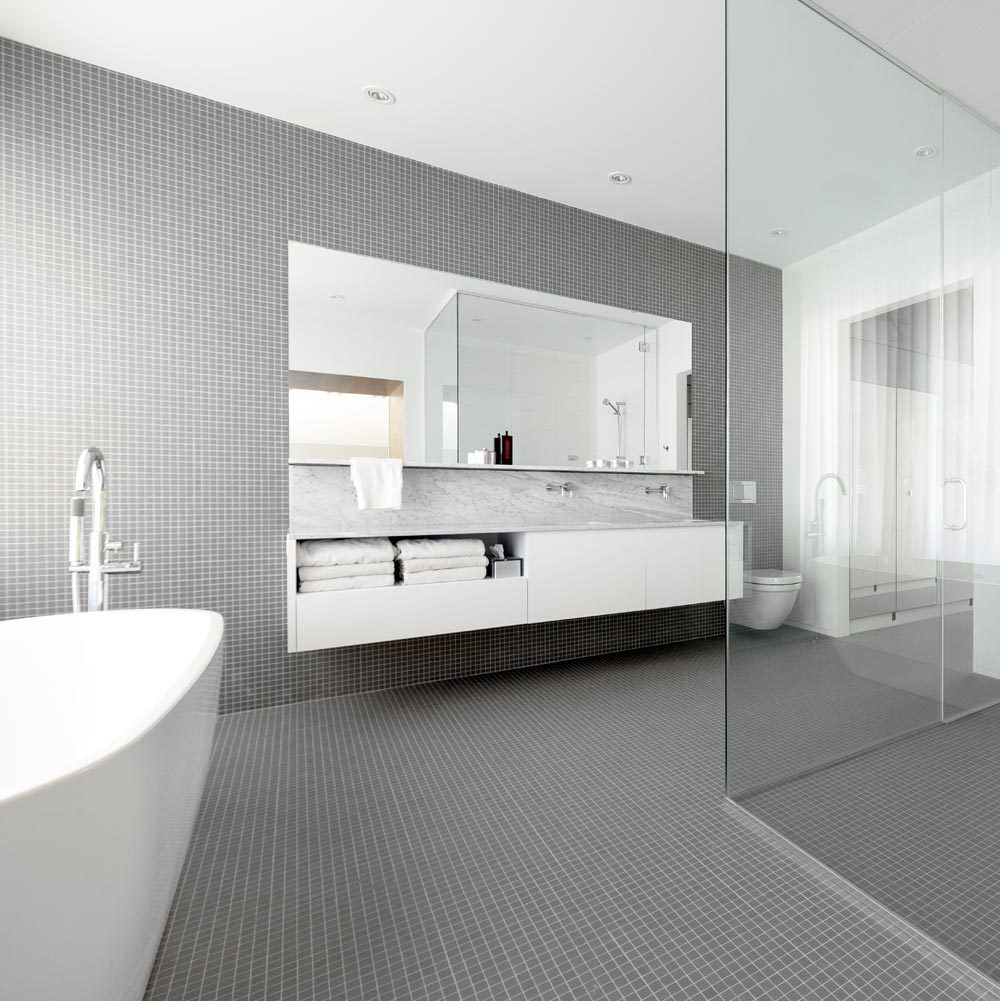 Pure white fixtures and grey mosaic tiles add a soothing touch to ...