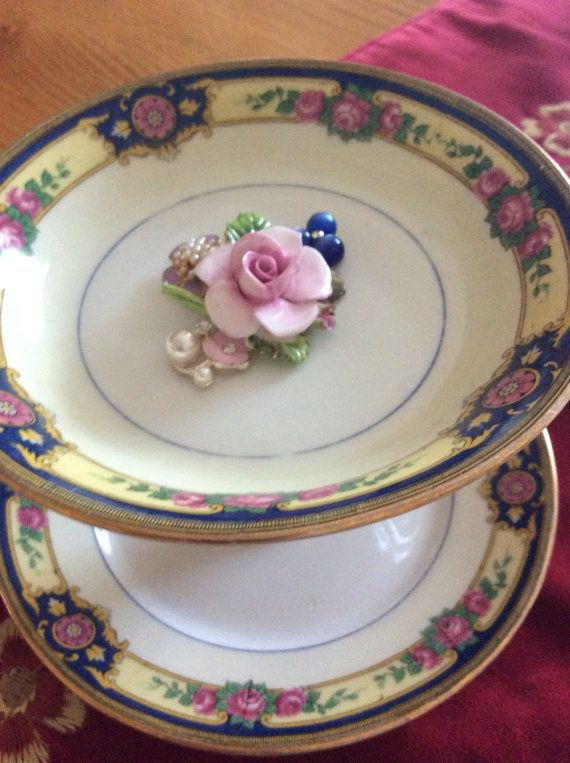 This item is a ring/jewelry holder. It is handcrafted out of vintage dishes,decorated with vintage jewelry. Top plate measures 5 inches and the bottom 6 inches. It is 4 inches in height.
