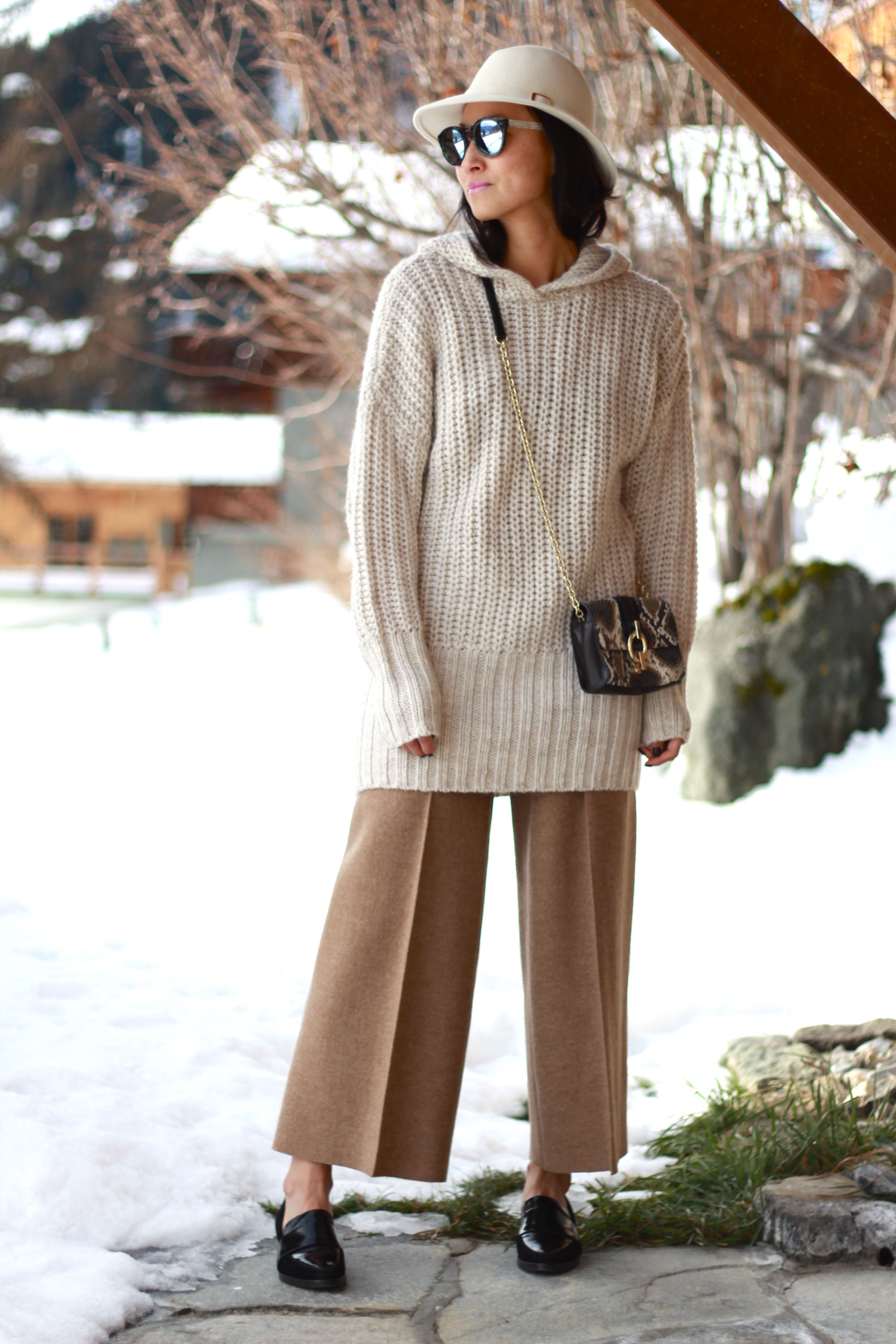 Shop this look on Lookastic:  http://lookastic.com/women/looks/hat-sunglasses-oversized-sweater-crossbody-bag-wide-leg-pants-loafers/7909  — White Wool Hat  — White and Black Sunglasses  — Beige Knit Oversized Sweater  — Black Snake Leather Crossbody Bag  — Tan Wide Leg Pants  — Black Leather Loafers