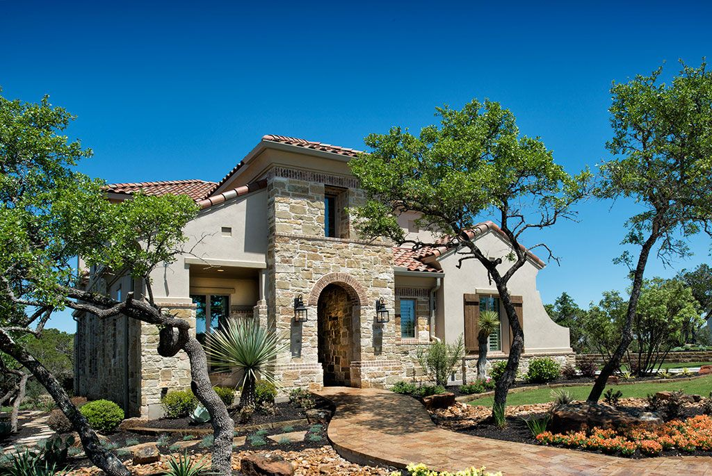 This Mediterranean-inspired exterior is highlighted with gorgeous native Hill Country landscaping. Highland Homes | Rough Hollow | Exterior | Lakeway, TX | Plan 617