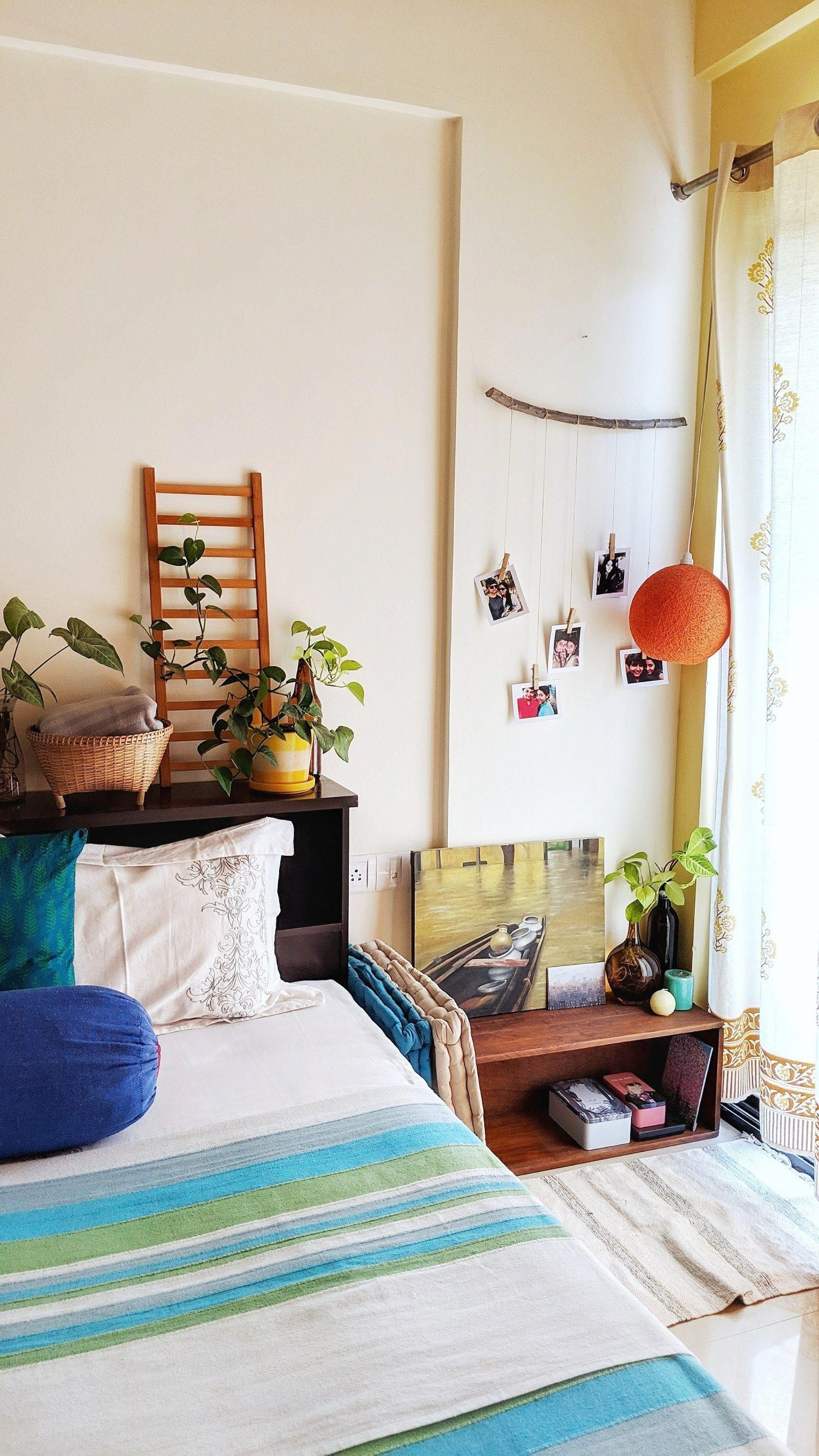 Jayati and Manali share their home tour as the science home décor - the bedroom is decorated with beautiful photos, hanging light, green plants, ladder and handpainted frame #indischesschlafzimmer