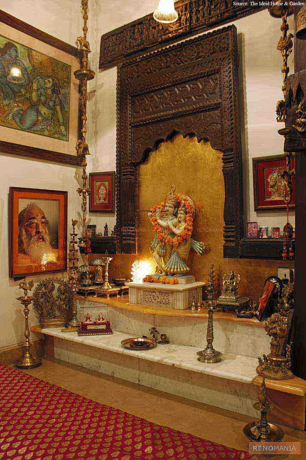 an elegant puja room with marble floor and hanging bells and idols