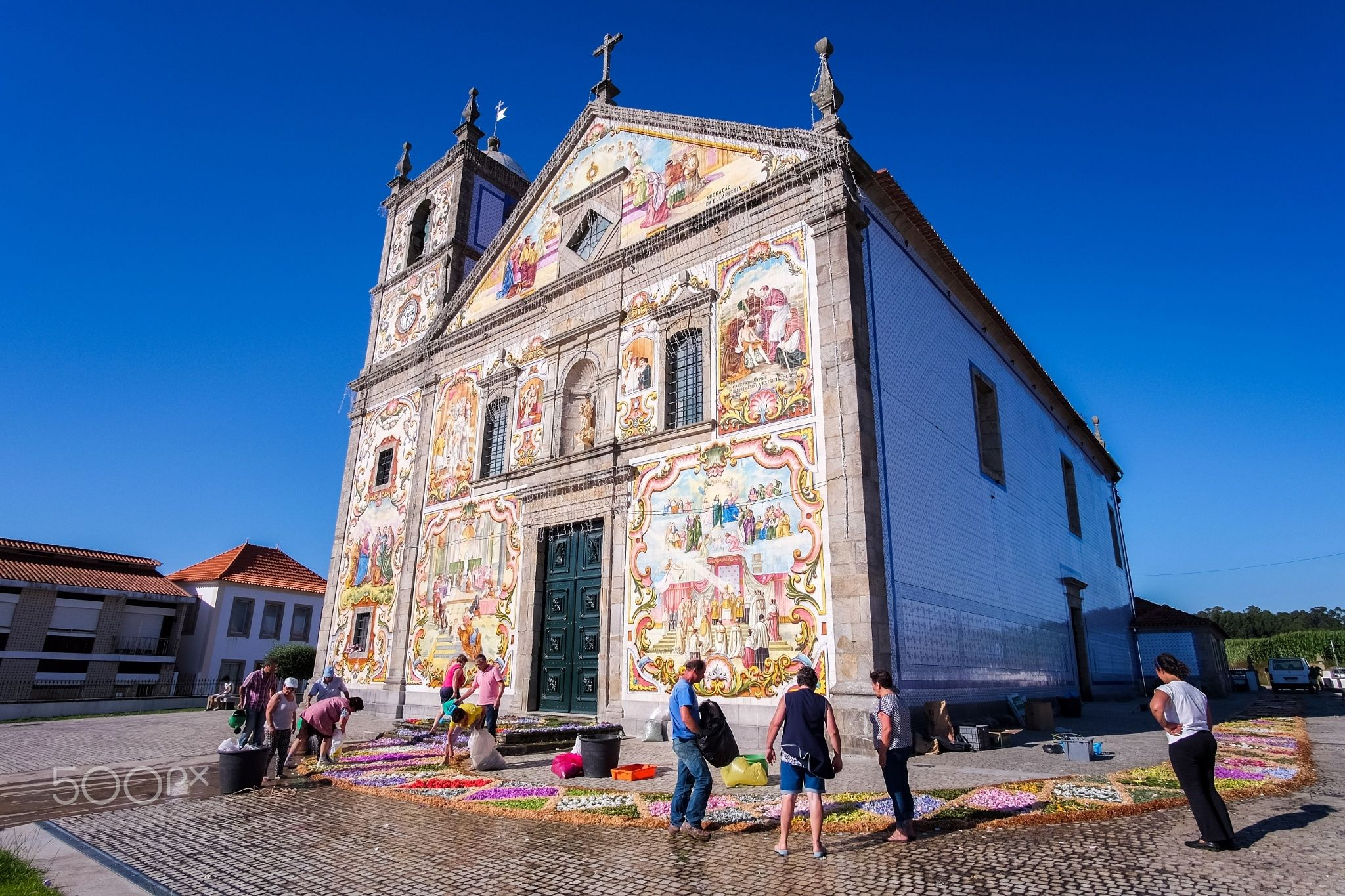 Jubilation - Locals prepare the decoration of the Válega church, to celebrate the jubilation on the priest.  This church is a masterpiece of the azulejo (painted, glazed tile) art and one of the most beautiful in Portugal. Sure worth a visit, especially at sunset, as the main façade faces west. The interior is also amazing, with an exotic wood ceiling and wonderful tiles covering the walls.  Válega is located near the town of Ovar and easy enough to reach from Porto.