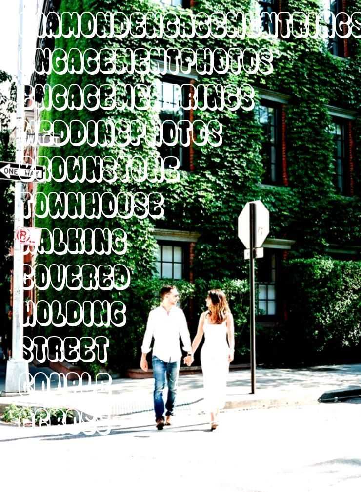 walking across New York City Street holding hands with Ivy Covered Browns  Couple walking across New York City Street holding hands with Ivy Covered Brownstone Townhouse...