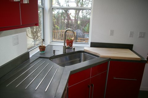 Custom designed concrete kitchen countertop with integrated cutting board and wash board.