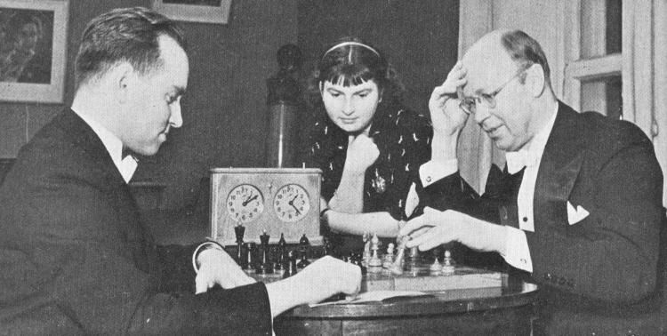Sergei Prokofiev playing chess against violinist David Oistrakh with violinist Liza Gilels watching.