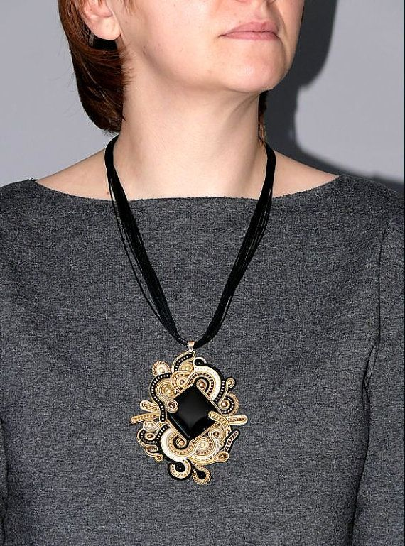 Beautiful, impressive soutache necklace, made from Soutache strings, Onyx, Hematite and glass beads. Pendant have been impregnated. Rear finished with natural leather. Full length: 4 inches. Length of string: 22 inches Colour: black, gold, beige and ecru.