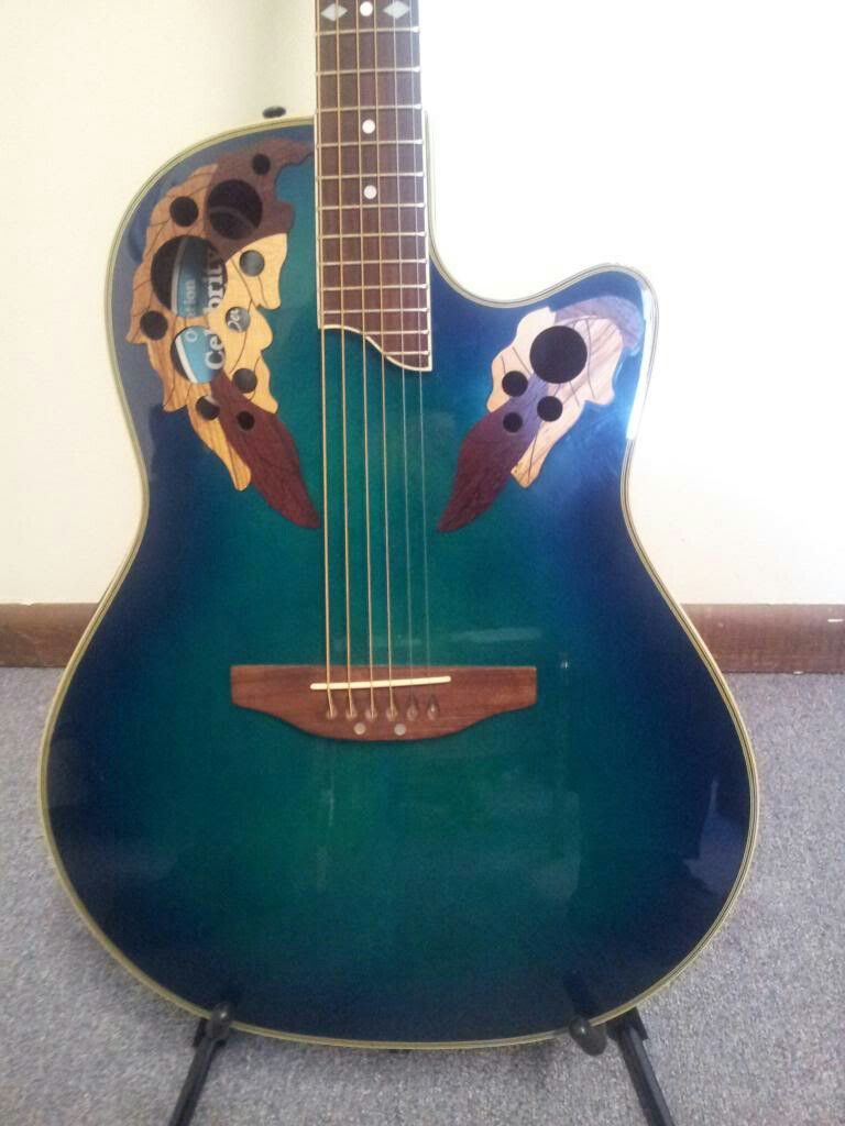 This Blue Green Ovation Guitar Is Beautiful With The Leaf Accents