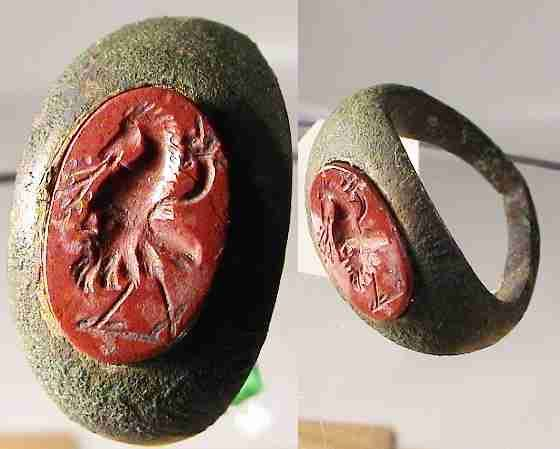 EdgarLOwen.com ANCIENT ROMAN ART 7743. ROMAN BRONZE RING, with a gnostic gem. The gem shows a horse head, standing on Ibis feets, carrying a cornuacopia and a kind of fruit in mouth. If you have a close look at the body, you can see that this is building a bearded bust looking to left ! Diameter is 2.3 cm. A rare type gnostic gem ! Intact, unlceaned condition.