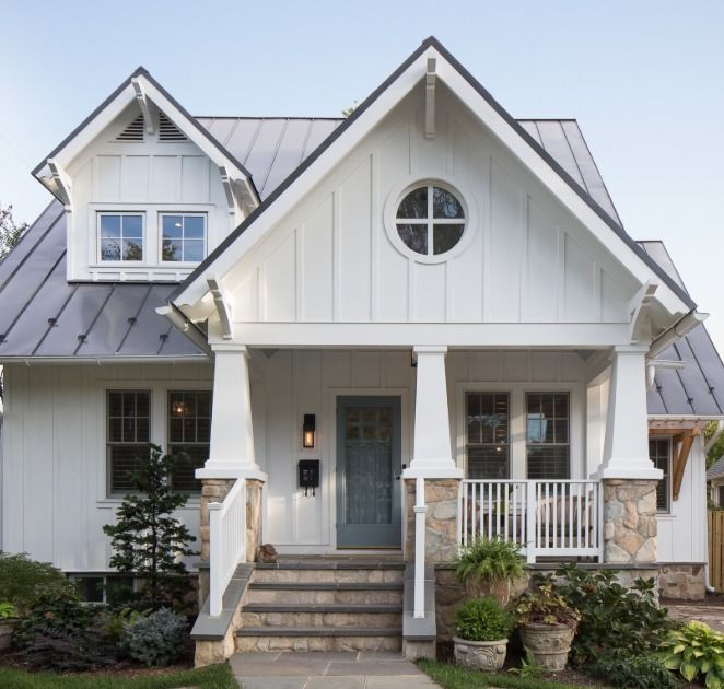 Charming white Craftsman house exterior with board and batten, round window, and stone detail…