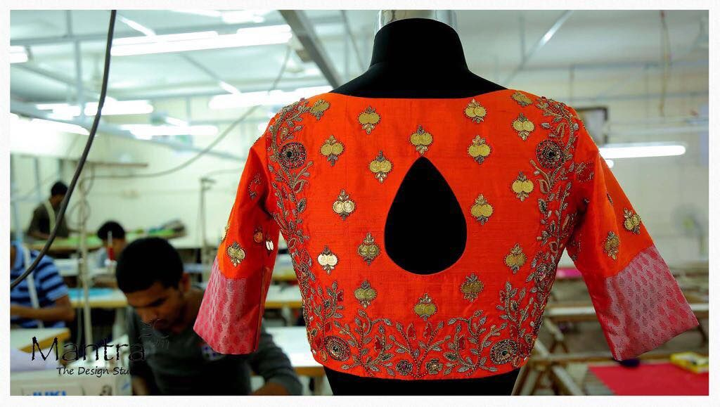 Beautiful orange designer blouse with floret lata design hand embroidery thread work from Mantra.