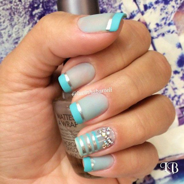 Blue gray and green blue themed French tips using silver metallic strips draped over the base as well as silver beads.