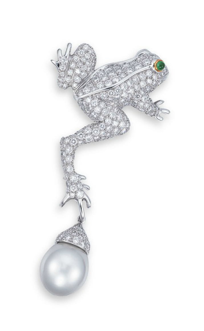 A CULTURED PEARL, DIAMOND AND EMERALD BROOCH, BY TIFFANY  CO.  Designed as a pavé-set brilliant-cut diamond frog with a cabochon emerald eye, suspending a detachable white cultured pearl drop measuring approximately 12.2 x 12.7 mm, mounted in platinum and 18k yellow gold, 6.6 cm long, in black suede Tiffany  Co. case Signed Tiffany  Co.