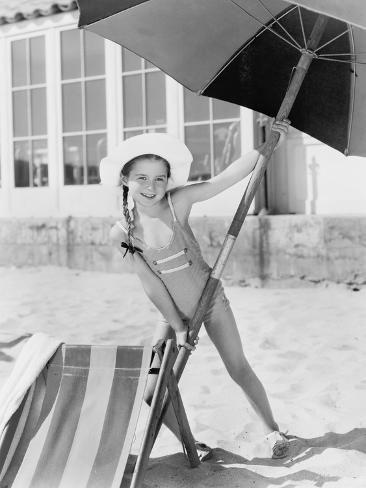 'Girl Placing a Large Umbrella into the Sand' Photo -   Art.com