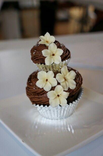 Cupcakec rema de chocolate dos pisos y flores de azucar