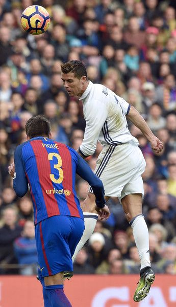 Real Madrid's Portuguese forward Cristiano Ronaldo (R) heads the ball beside Barcelona's defender Gerard Pique during the Spanish league football match FC Barcelona vs Real Madrid CF at the Camp Nou stadium in Barcelona on December 3, 2016. / AFP / LLUIS GENE