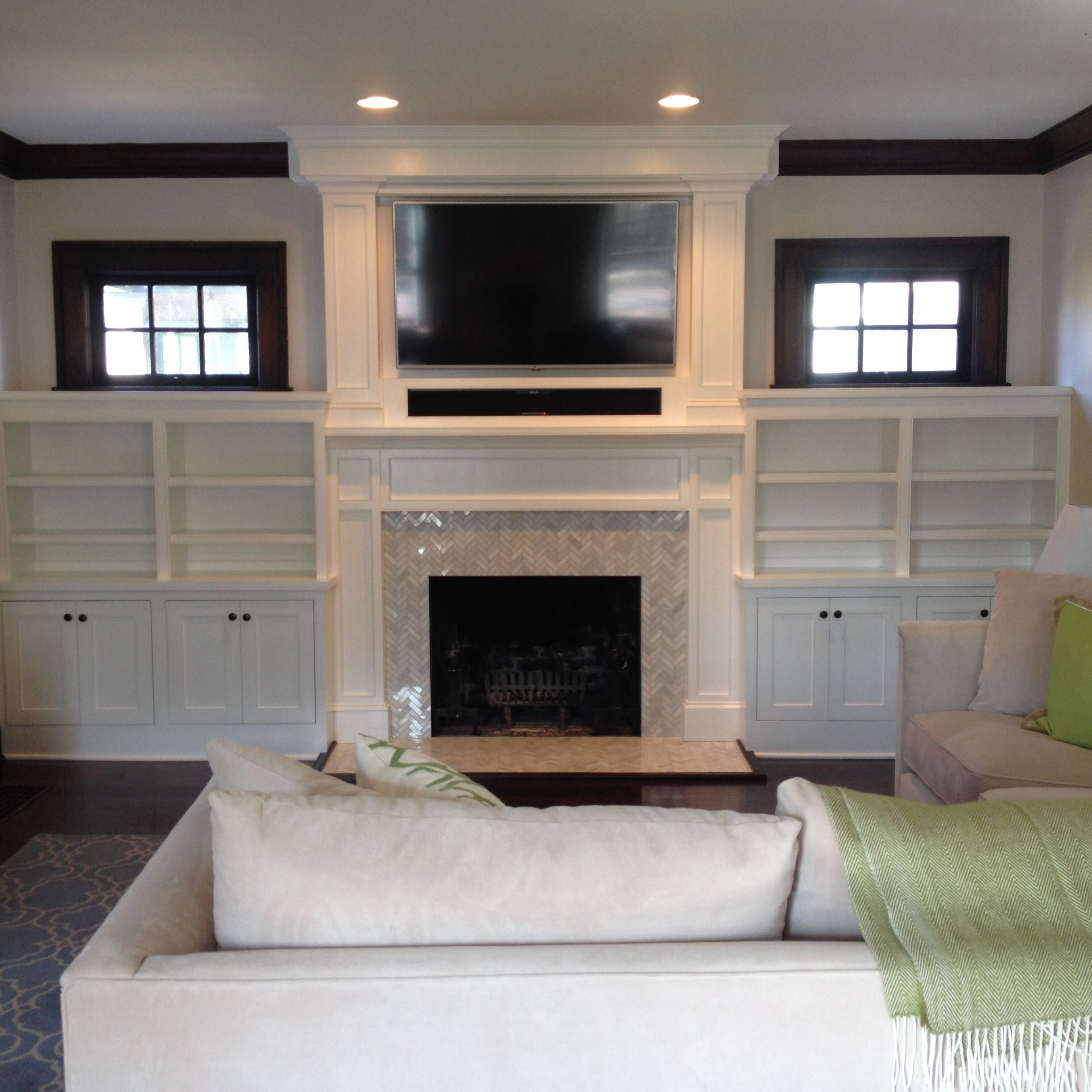 Built ins around our fireplace with herringbone marble tile tv