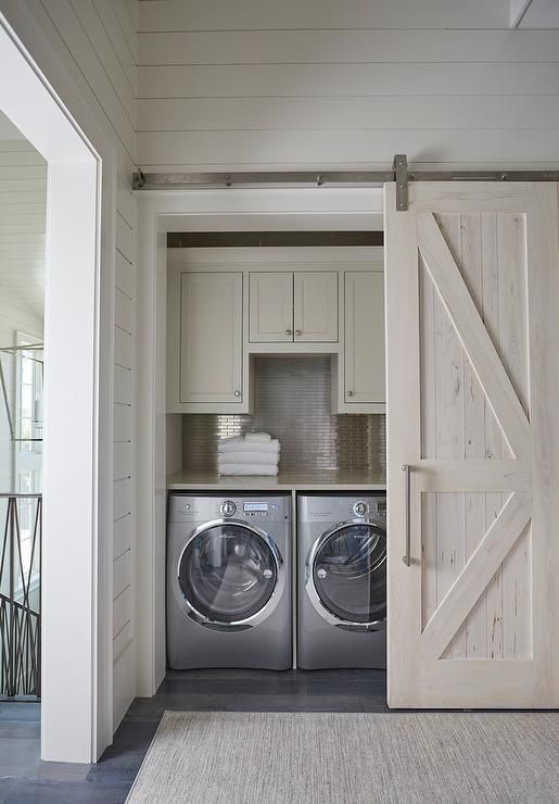 A pecky cypress barn door on rails opens to a hallway laundry room filled with light gray shaker cabinets suspended over a stainless steel mini brick tile backsplash and an enclosed washer and dryer.