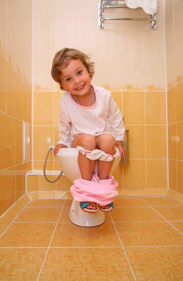 Young Woman Sitting On Toilet Using Phone High-Res Stock