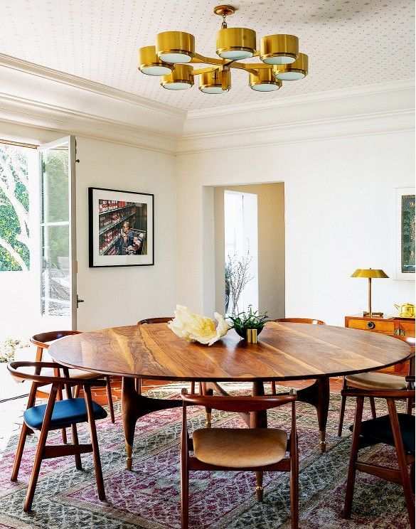 Modern Midcentury Dining Space With Large Round Wood Table And Gold Light Fixture