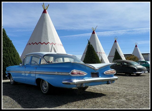 """""""A 1959 Impala (along with an old Hudson and a 1956 Buick in the background) sits in front of some of the 'rooms"""" at the Wigwam Village along Route 66 in Holbrook, Arizona."""""""