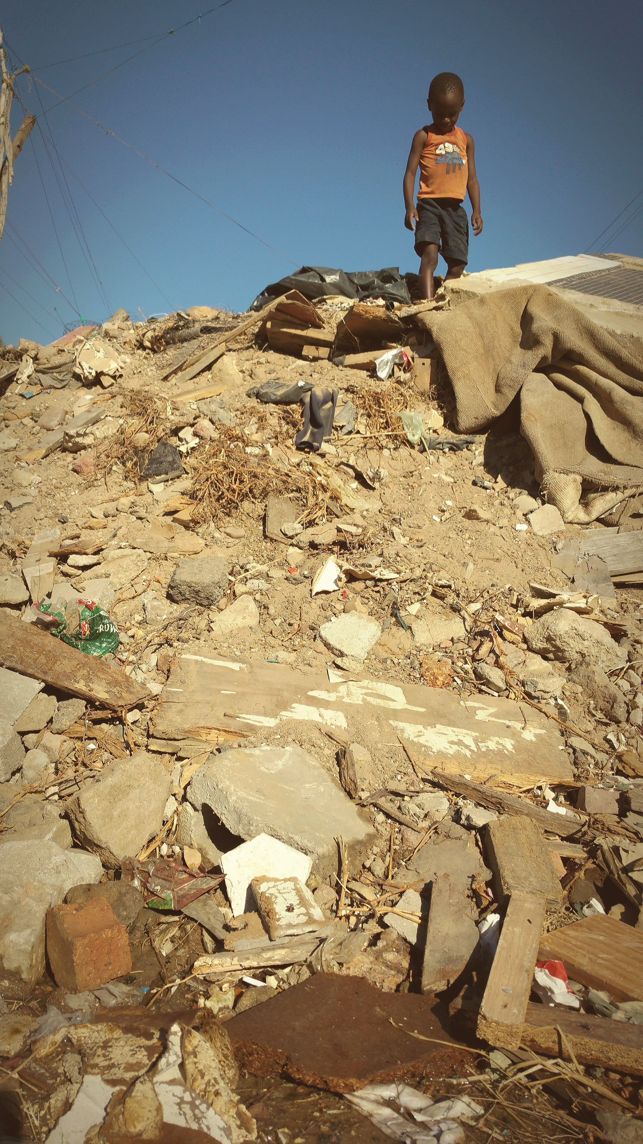 a little boy on a pile of rubble and rubbish