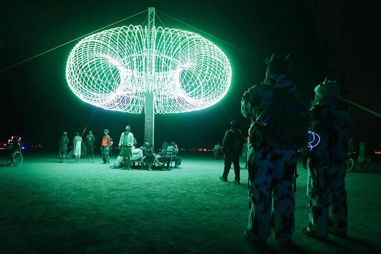 """People explore an art installation during the Burning Man 2012 """"Fertility 2.0"""" arts and music festival in the Black Rock Desert of Nevada"""