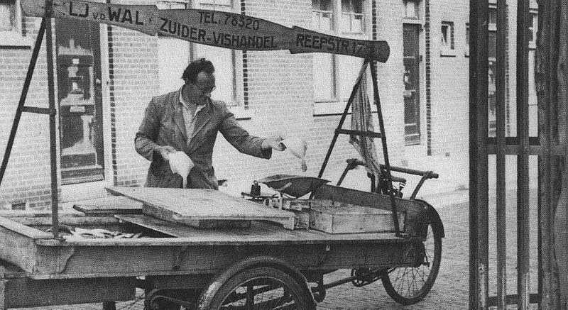 De visboer. Bij ons vroeger op het Vaste Land,bij de zeemansbeurs,in Rotterdam,was ook zo'n visboer.(niet deze meneer) Hij verkocht ook grote zure bommen. Zelf heb ik wel gezien,dat als er een dronke zeeman een harinkje wou hebben,gaf hij een vorentje.