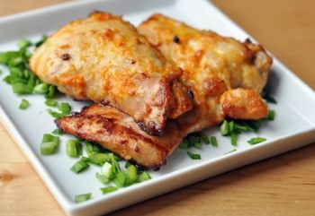 Освободите курицу от костей, осушите. Перемешайте соевую и имбирную пасту, чеснок, цедру одного лимона, 2 ст. ложки оливкового масла, чтобы получилась однородная паста, обваляйте курицу и замаринуйте на ночь в холодильнике или немедленно обжарьте в духовке.  Нагрейте духовку до 220 градусов, выложите курицу в один слой на противень, поджарьте в течение получаса, перевернув ее на другую сторону спустя 15 мин. Выньте противень и остудите курицу в течение 5 мин, после чего сразу же подавайте.